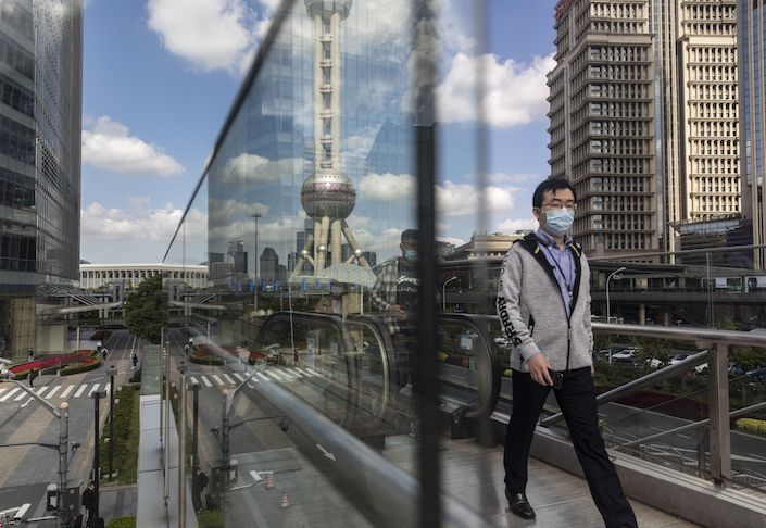 Morning commuters wearing protective mask ride an escalator in the Lujiazui Financial District in Shanghai.