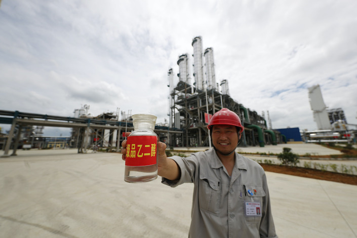 A worker holds a bottle of ethylene glycol made in a factory in Guizhou.
