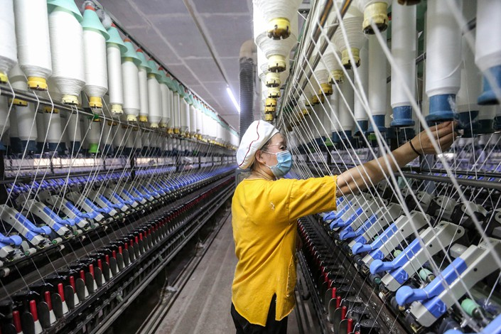 A worker examines machinery on July 1 at a textile plant in Huaian, East China's Jiangsu province.