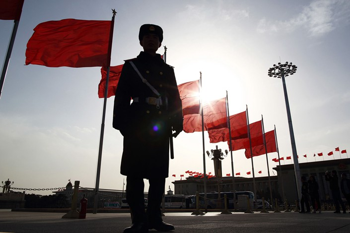 A paramilitary police officer stands guard in front of red flags at Tiananmen Square in Beijing on March 2, 2015. Photo: Bloomberg