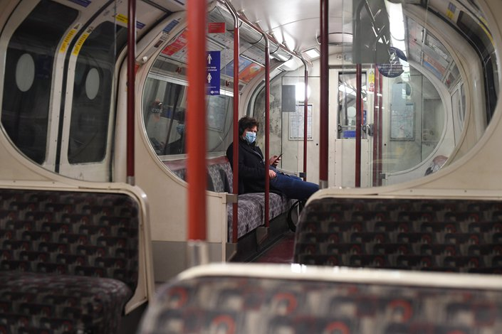A lone passenger rides the subway in London on Sunday, the first day of the city was under the country's strictest disease control measures.