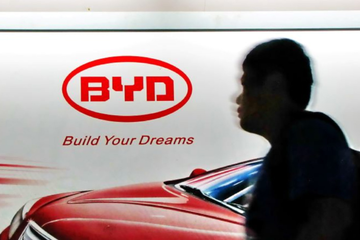 A man walks past a billboard advertising BYD cars in Shanghai on Sept. 9, 2011.