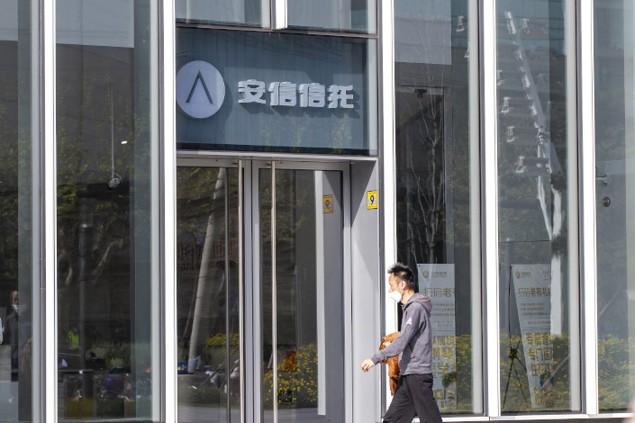 A man walks past an Anxin Trust office in Shanghai on April 7.