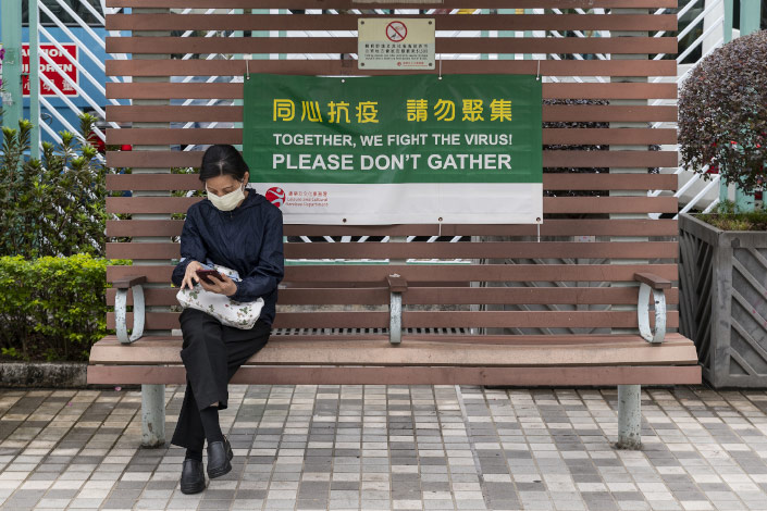 A woman checks her phone on Dec. 16 on a bench featuring a public service announcement reminding people of avoid gatherings in Hong Kong.