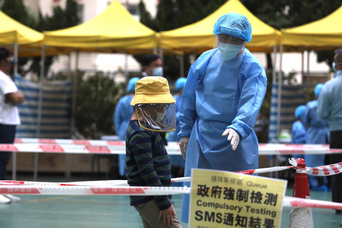 A medical worker talks to a child waiting to take a nucleic acid test on Dec. 10 in Hong Kong.