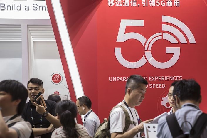 Attendees stand in front of a 5G sign during the CES Asia Show in Shanghai