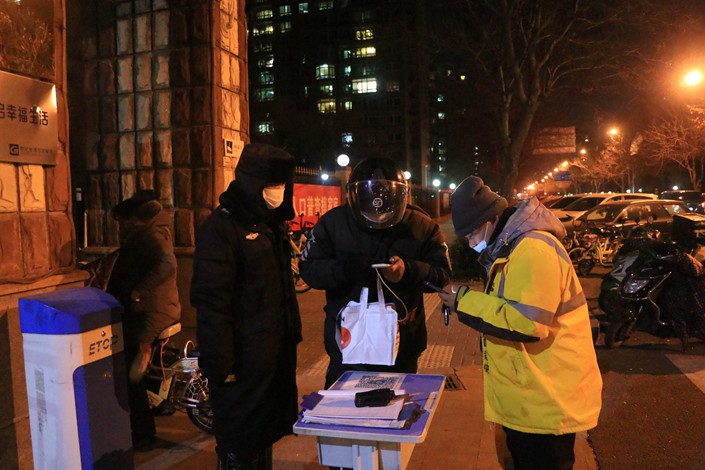 Beijing residents get their health information checked on Tuesday after a recent flare-up of Covid-19.