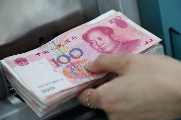 An employee places genuine Chinese one-hundred yuan banknotes into a counting machine