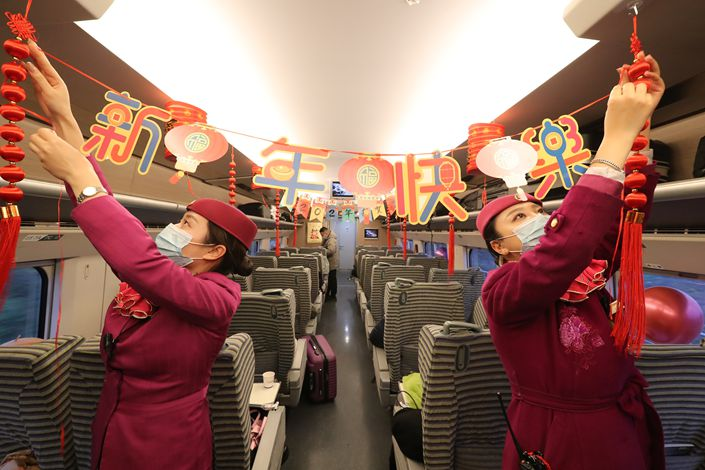 Train attendants decorate a New Year's Day themed car on a high-speed train in Southwest China's Chongqing municipality on Dec. 31, 2020.