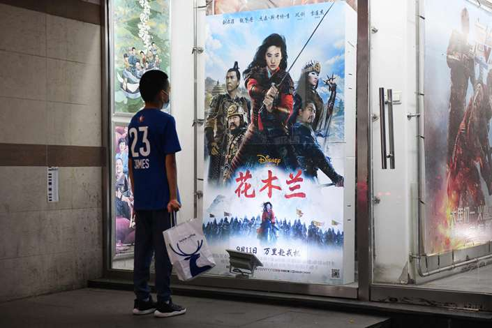 A boy looks at poster of the Disney movie