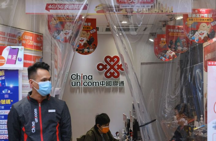 Sales assistants work at a China Unicom Hong Kong Ltd. store in Hong Kong.