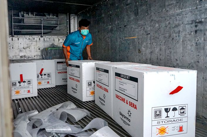 Works unload boxes of Sinovac's Covid-19 vaccine on Tuesday in Pekanbaru, Indonesia.