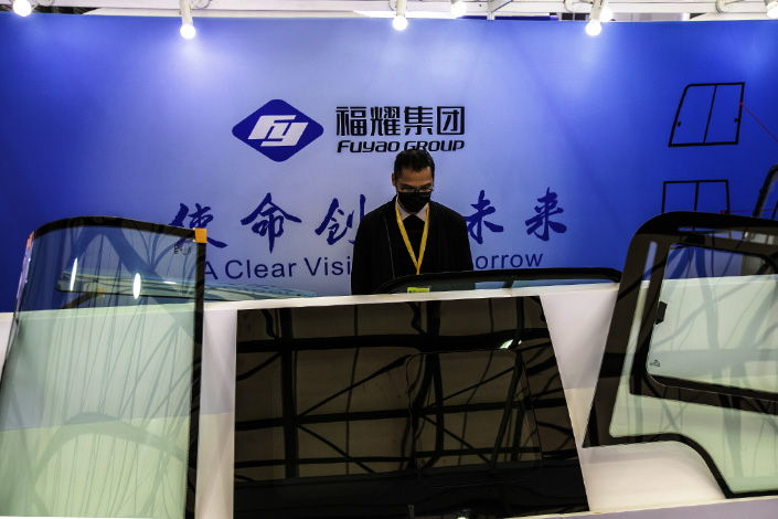A man checks out a car windshield made by Fuyao at an exhibition in Shanghai on Nov. 25.