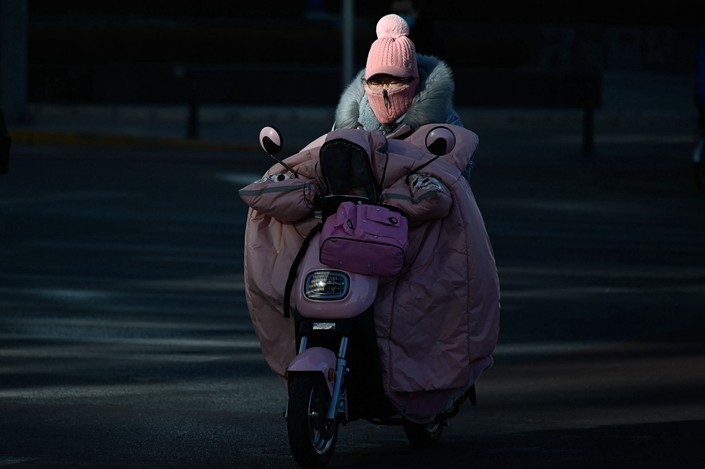 A woman wrapped up for the cold in Beijing on Jan. 8. The city last week recorded its lowest temperature since 1966. Photo: Bloomberg