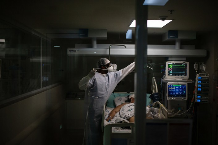 A health care worker works with a patient in the Covid-19 intensive care unit at the Emilio Ribas Institute of Infectious Disease hospital in Sao Paulo. Photo: Bloomberg