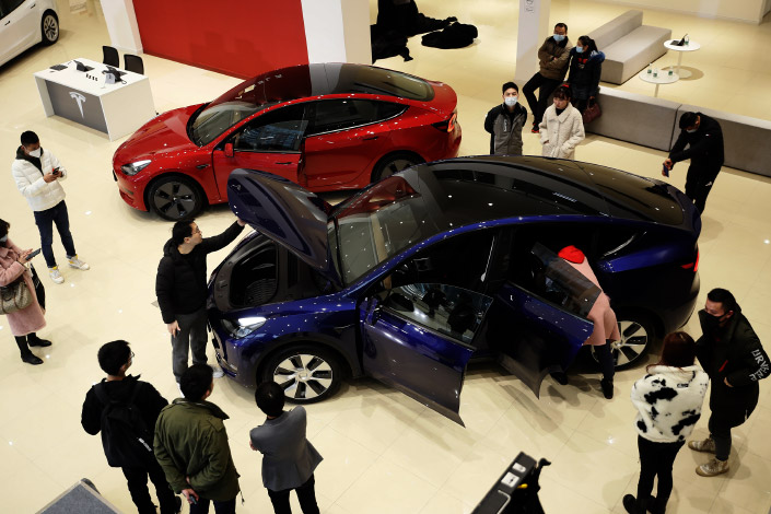 Prospective car buyers gather around a Tesla Model Y on Tuesday at a showroom in Southwest China's Chongqing municipality.