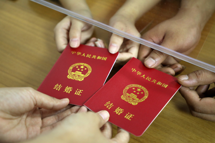 A couple receives their marriage certificates on Aug. 25 in Binzhou, East China's Shandong province.