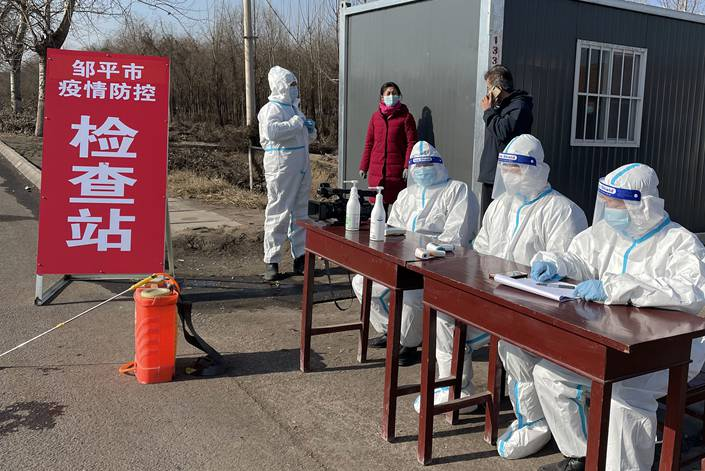 Volunteers man a checkpoint at the entrance to a village in Changshan Town, Zouping, Shandong province on Jan. 17.
