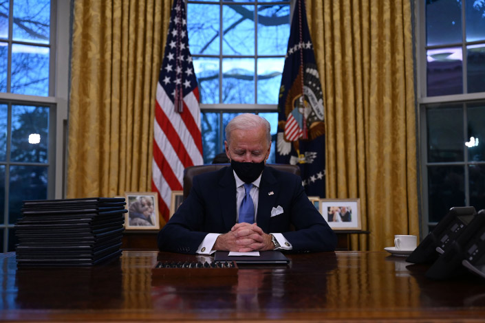 U.S. President Joe Biden sits in the Oval Office on Jan. 20.