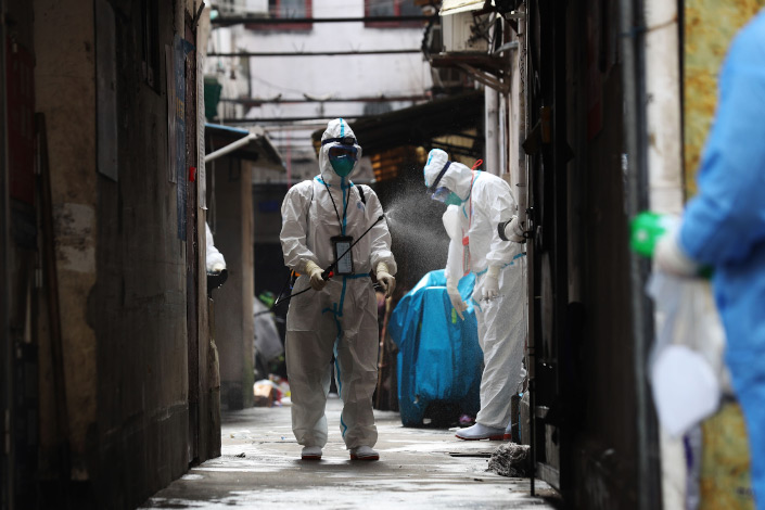 A medical worker in protective gear disinfects a residential community in Shanghai on Jan 27.