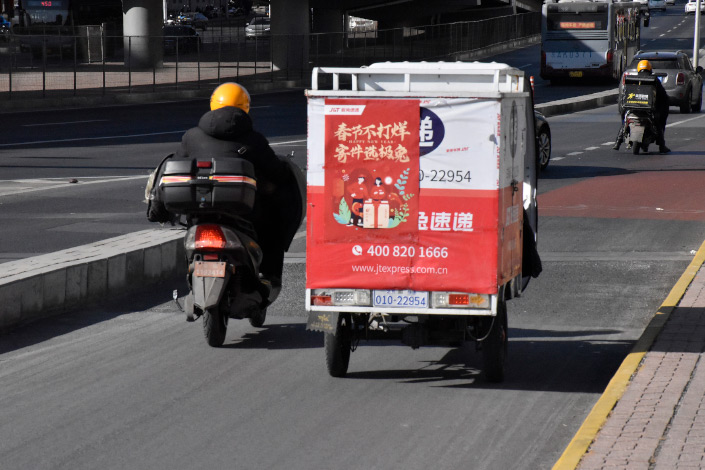 A delivery driver delivers parcels in Beijing on Thursday.