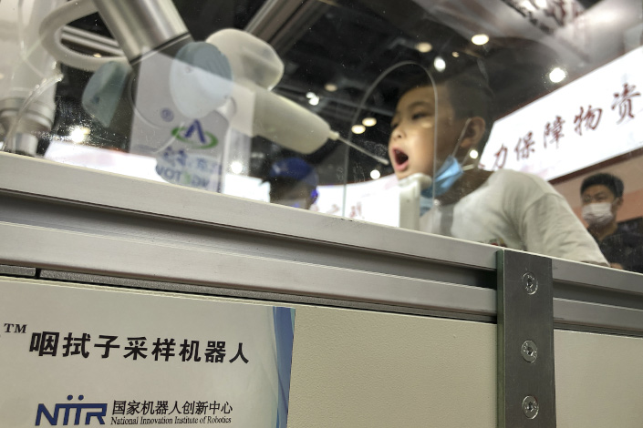 A child tries out an throat swab sampling robot at an exhibition in Beijing on Sept. 6.