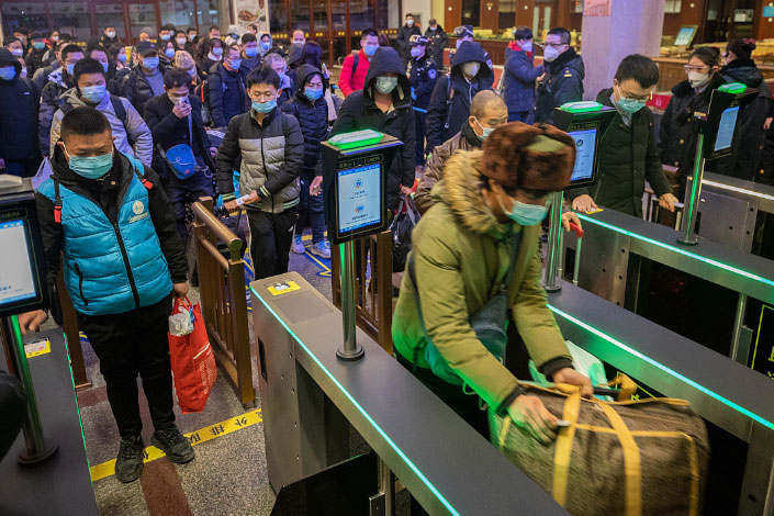 Passengers line up to check in at Beijing railway station on Thursday.