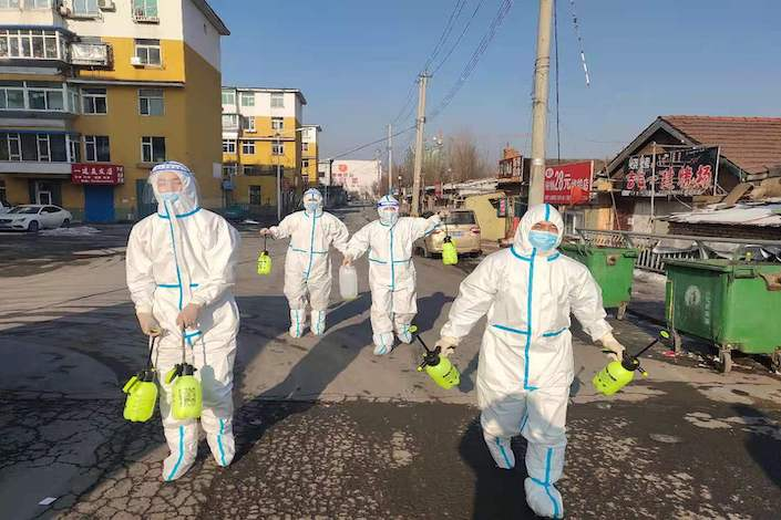 Volunteers wearing protective clothing disinfect a residential area in Tonghua, Jilin province, Jan 22, 2021.