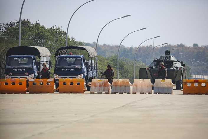 Soldiers and police vehicles block the road near parliament in Naypyidaw, Myanmar, on Monday. Photo: VCG