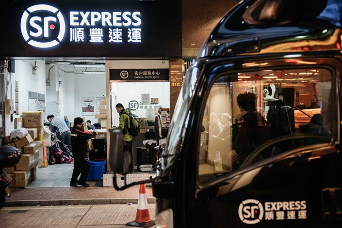 Employees handle packages at an SF Express location in Hong Kong in February 2017. Photo: Bloomberg