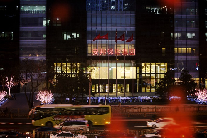 Traffic moves along a road in front of the entrance to the Anbang Financial Center at night in Beijing on Feb. 24, 2018. Photo: Bloomberg
