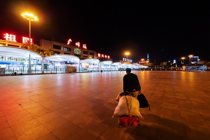 A passenger in the Guangzhou Railway Station Feb. 11.