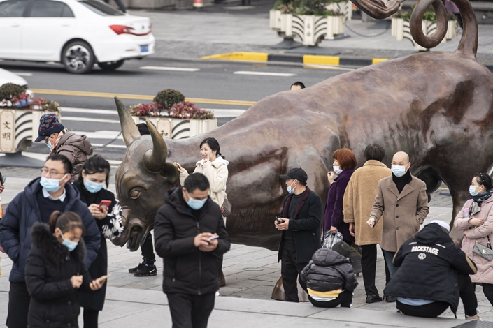 A woman poses for a photograph Friday alongside the Bund Bull in Shanghai. Photo: Bloomberg