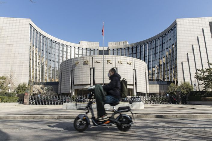 A motorcyclist wearing a protective mask rides past the People's Bank of China (PBOC) building in Beijing