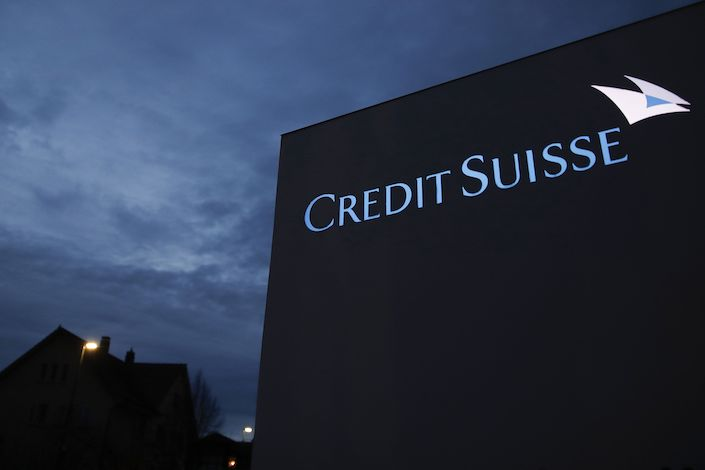 An illuminated Credit Suisse sign outside a Credit Suisse Group AG office building at night in Muri