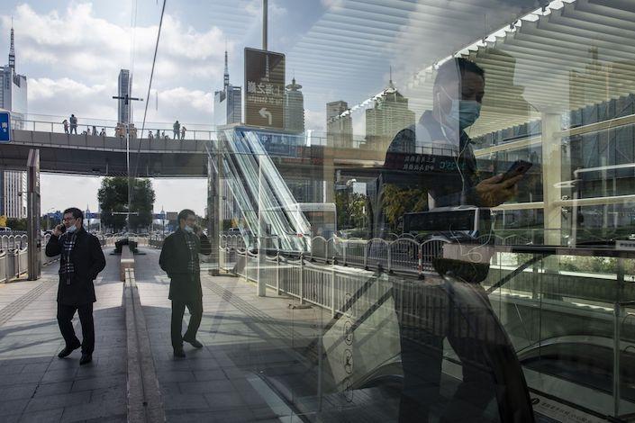 Pedestrians walk through the Lujiazui financial district in Shanghai