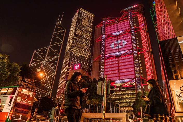 Pedestrians pass the illuminated HSBC headquarters at night in Hong Kong on Monday, Jan. 25. Photo: Bloomberg