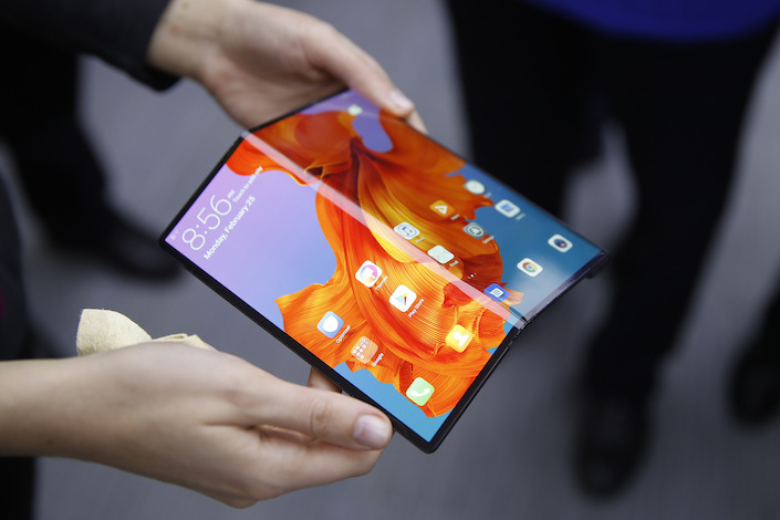An employee demonstrates a Mate X foldable 5G mobile device at the Huawei pavilion on the opening day of the MWC Barcelona in Barcelona in 2019