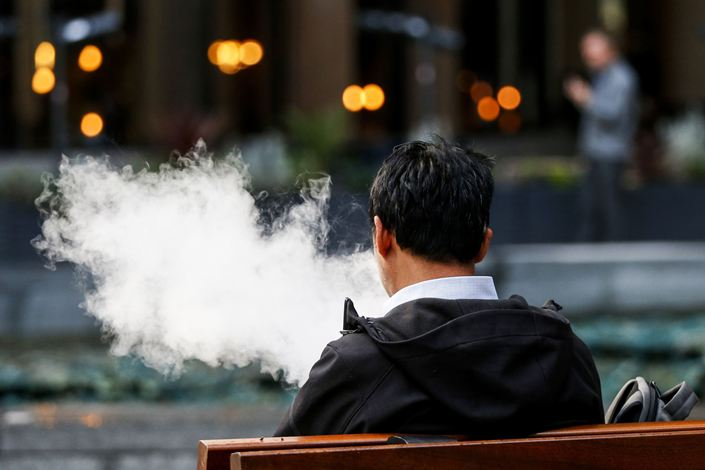 A pedestrian exhales a cloud of vapor from a vaping device in London. Photo: Bloomberg