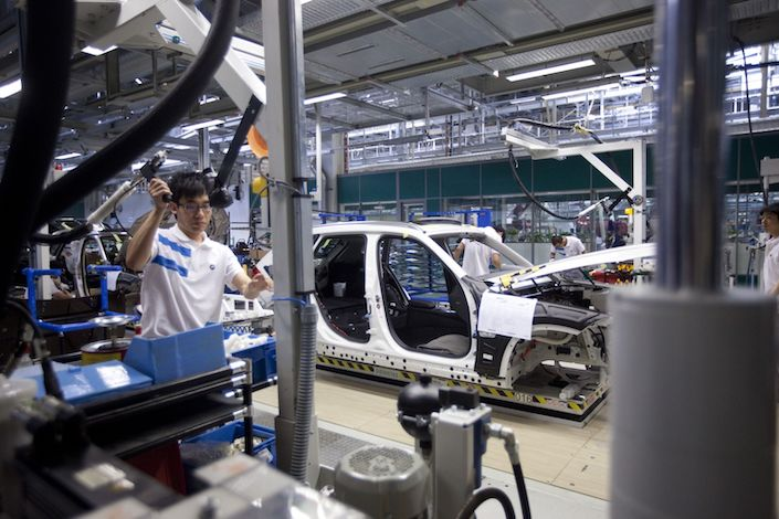 Employees at the BMW Brilliance Automotive Ltd. Tiexi plant work on the glass installation assembly line in Tiexi
