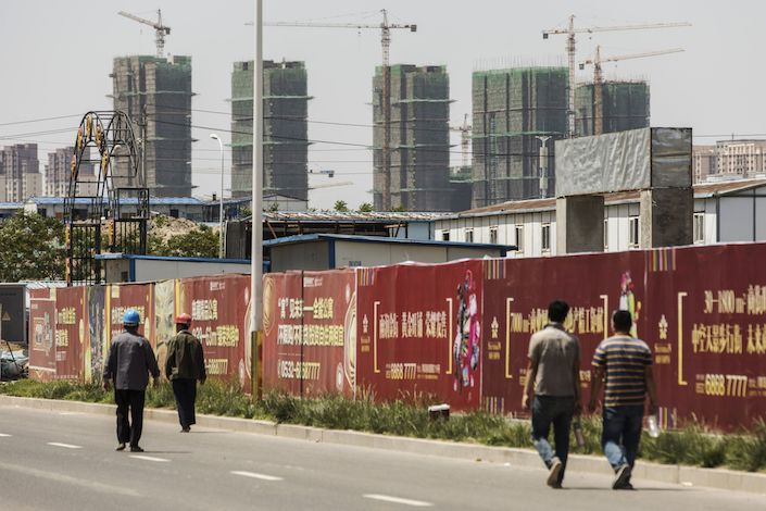Workers walk along a road as residential buildings stand under construction in Qingdao