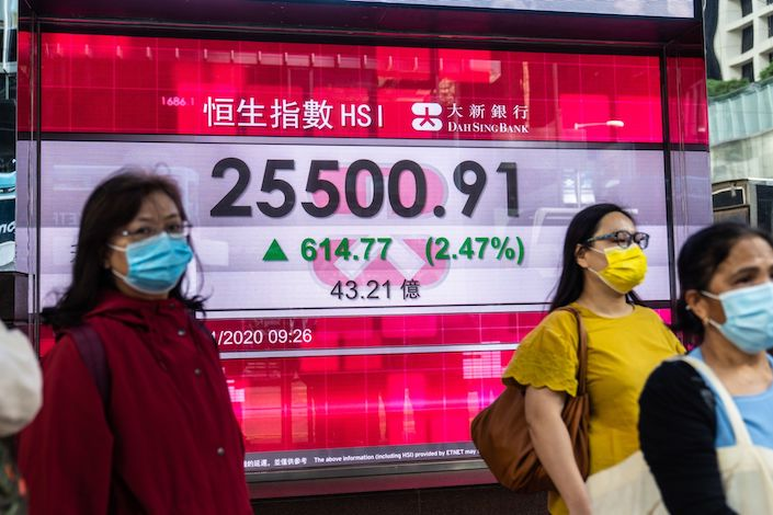 Pedestrians wearing protective masks walk past an electronic screen displaying the opening figure of the Hang Seng Index in Hong Kong
