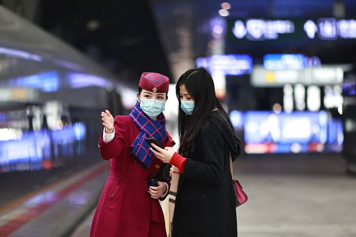 A train attendant gives directions to a passenger at a railway station in Chongqing in Southwest China on Feb. 11. Photo: VCG