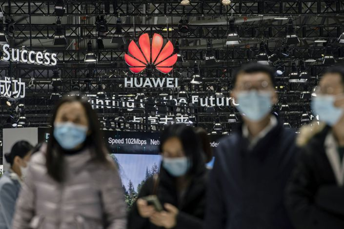 Attendees walk past Huawei's logo at an exhibition in Shanghai on Feb. 23. Photo: Bloomberg