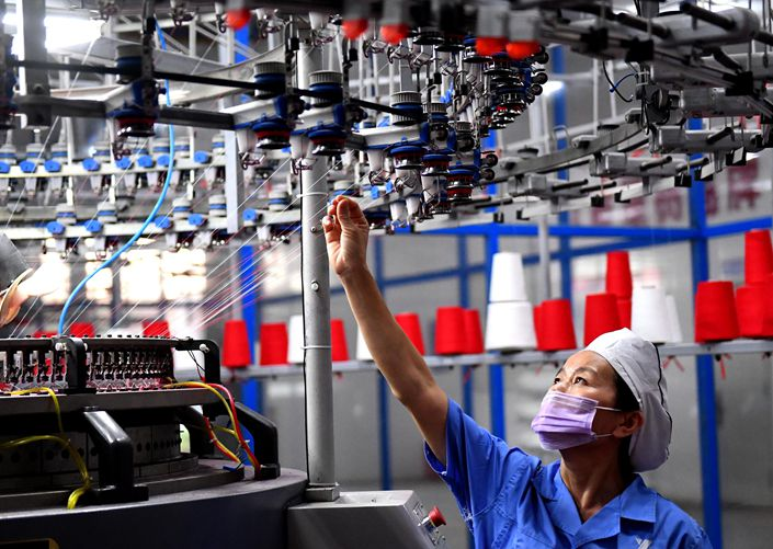 An employee works at textiles factory in Shangqiu, Henan province, on Sept. 7, 2020. Photo: VCG