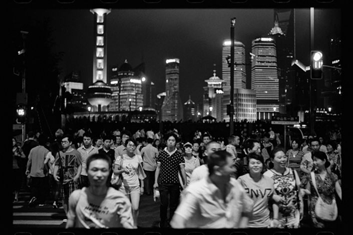 Visitors cross a main street at the Bund against a backdrop of the Pudong financial district in Shanghai
