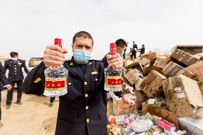 A staff member of China's national market regulator on Sunday holds up bottles of counterfeit booze about to be destroyed in Kuqa, Northwest China's Xinjiang Uyghur autonomous region. Photo: The Paper