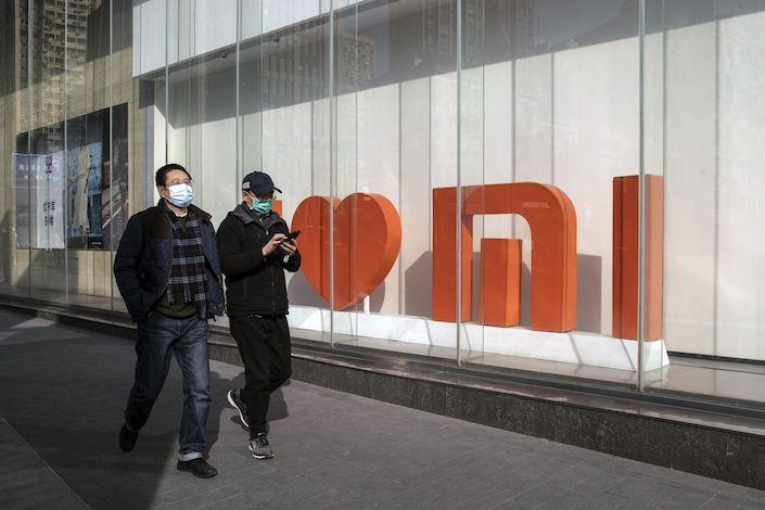 Pedestrians walk past a Xiaomi Corp. flagship store in Shanghai.