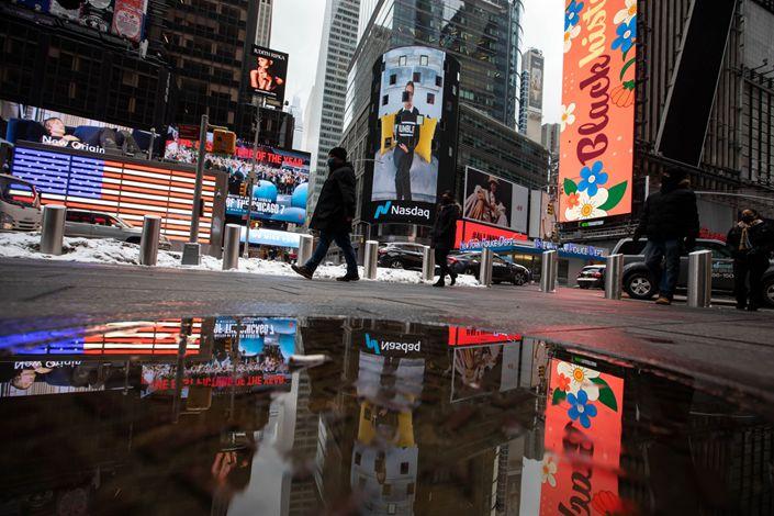 Pedestrians pass in front of the Nasdaq MarketSite in New York on Feb. 11, 2021. Photo: Bloomberg