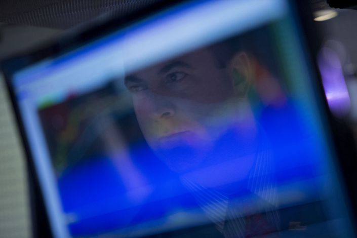 A trader is reflected on a computer screen while working on the floor of the New York Stock Exchange in New York in August 2013. Photo: Bloomberg